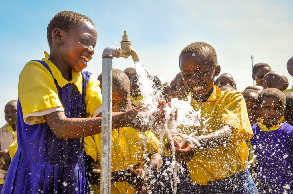 """©World Vision  Children celebrate the arrival of clean drinking water at their school, Wema ADP, Kenya. Before the project was initiated, children depended on water with high saline from a lake near their school. """"The first thing that I could do when I got home after school every evening was to get the donkey and my elder brother, descend to fetch water from the spring down a valley."""" Cases of water-borne diseases were common, particularly among children. 2/20/13 Summary: Water is chronically scarce in Kenya and continually diminishing due to climate change and a growing population. Compounding this problem is the poor quality of available water which is often polluted or high in saline and other unsafe minerals. Access to safe water is often the top priority need identified by rural communities. In many areas, women and children are forced to walk several miles each day in search of water. Photos of World Vision's response to this challenge. Africa"""